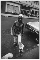 New York (Woman Wearing Scarf and Bell-Bottoms Stepping onto Curb) (1965) by Garry Winogrand
