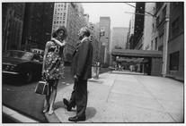 Untitled (Woman in Floral Dress Talking to Man on Street Corner) (1971) by Garry Winogrand