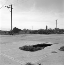 From Angel City West (hole in sidewalk) (1983) by Mark Steinmetz
