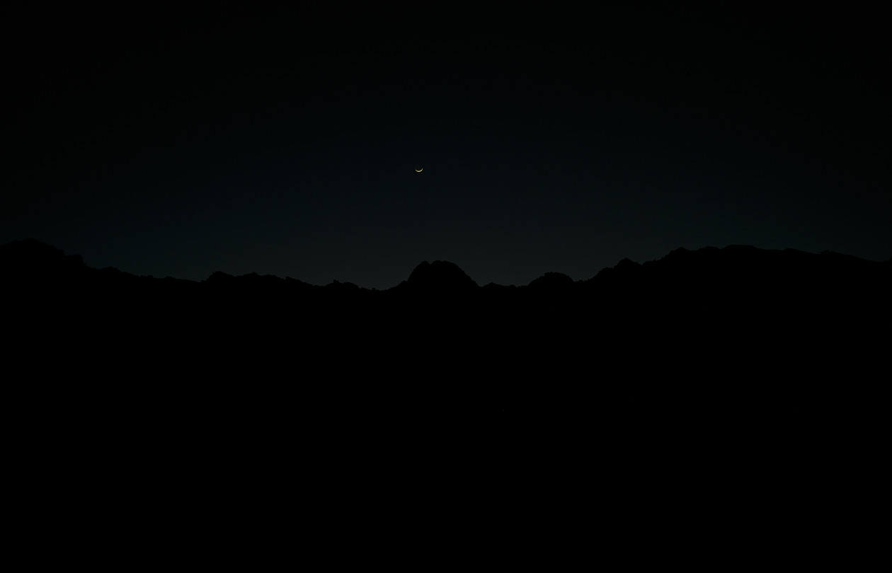 Crescent moon in blackness, Goldwater Bombing Range (2014) by Mark Klett