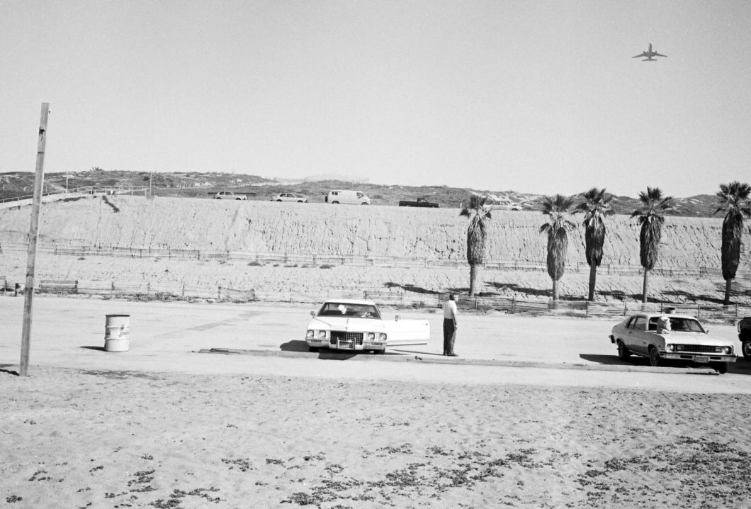 From Angel City West (man by white car with plane) (1983) by Mark Steinmetz