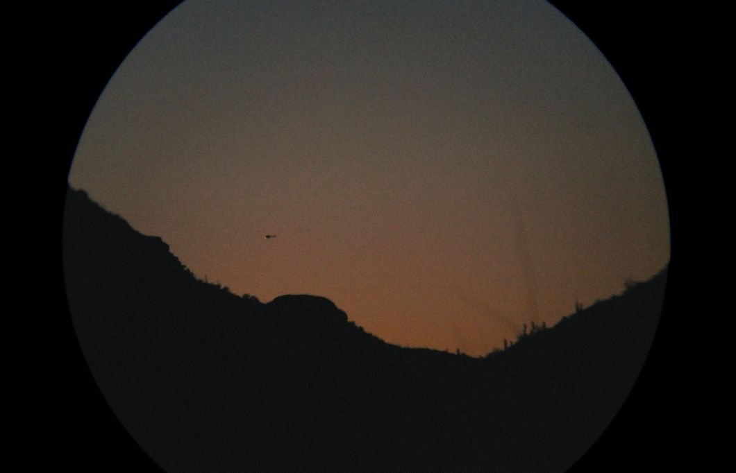 Hovering over smugglers: Border Patrol helicopter through binoculars at sunset (2013) by Mark Klett