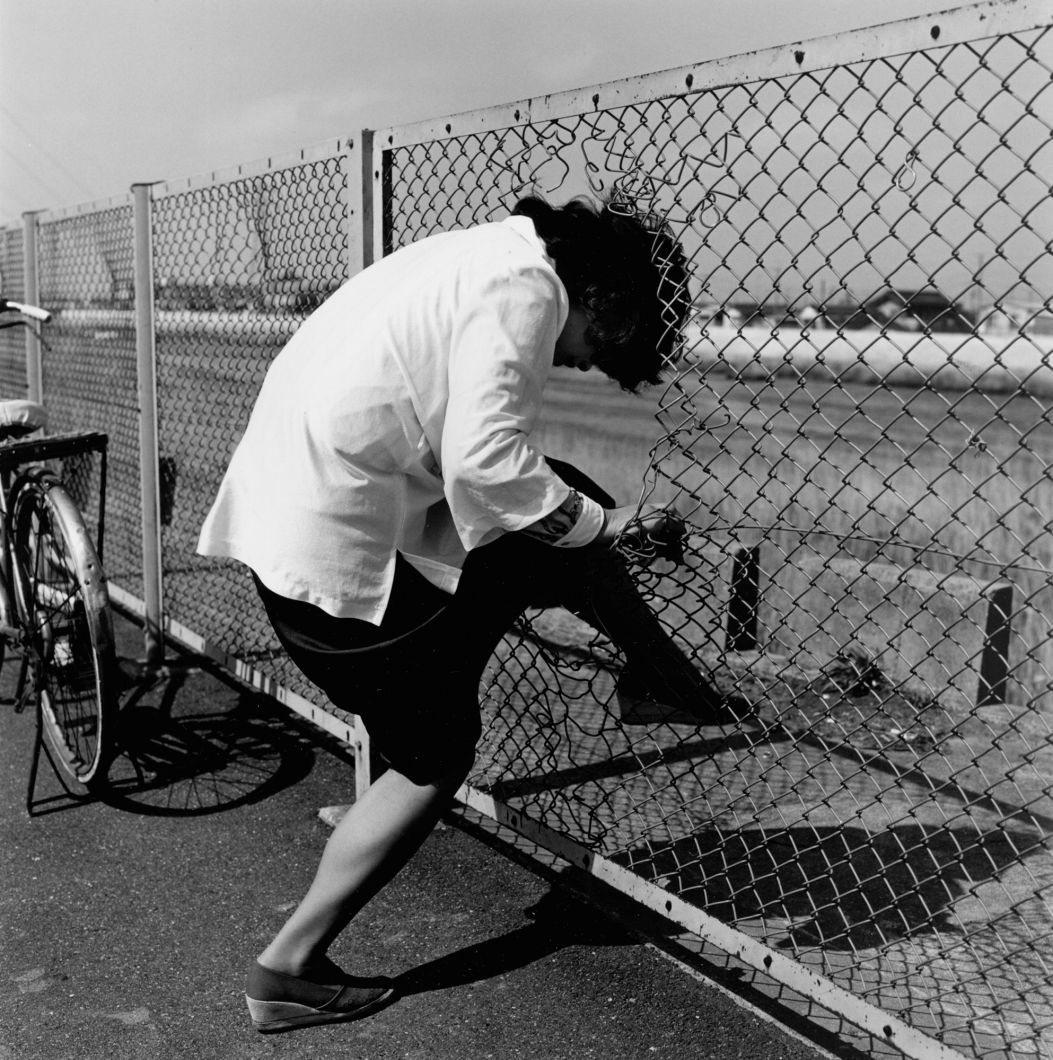 From Tokyokei (Woman passing the wire netting) (1970's - 1980's) by Issei Suda