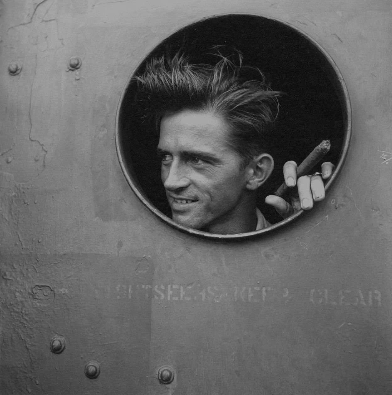 Pacific Theater, WWII (sailor smoking and peeking out of window) (1942-45) by Wayne Miller