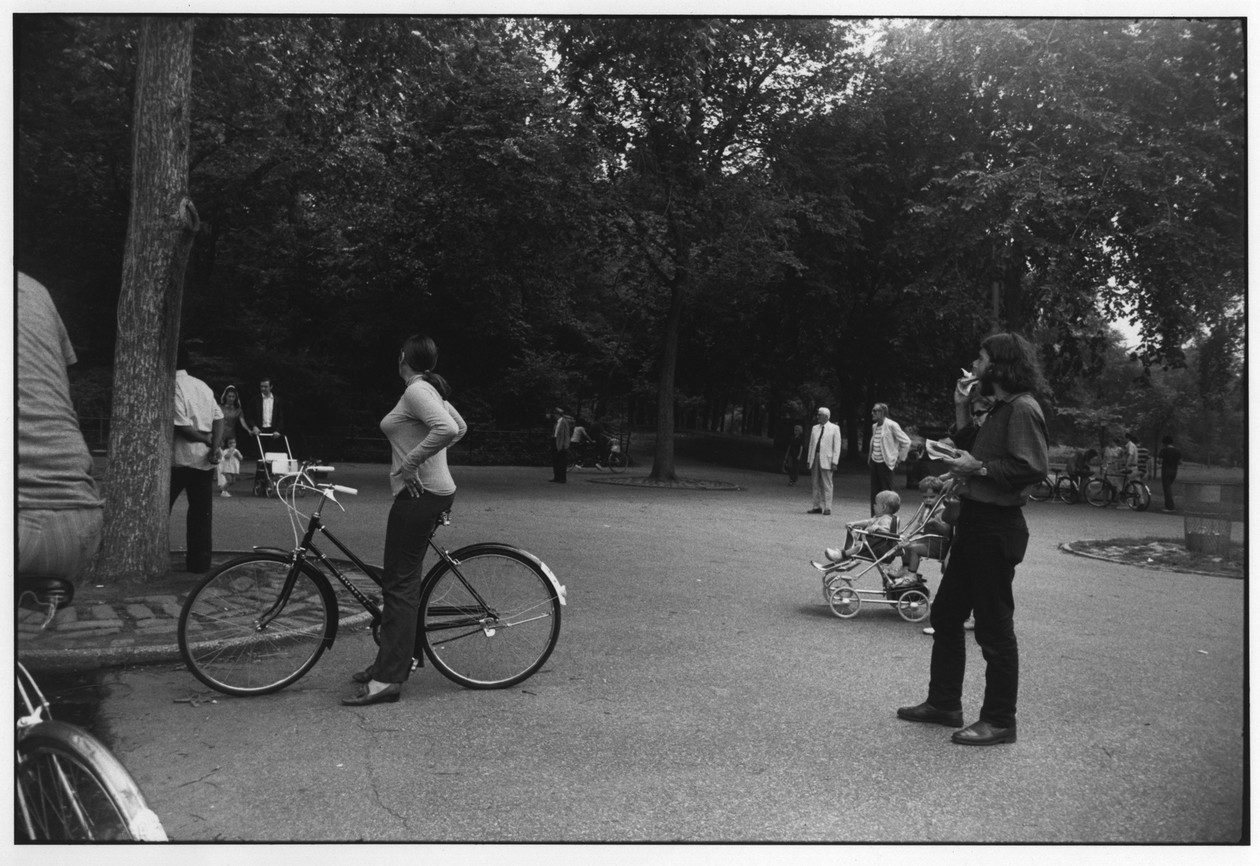 Untitled (Woman on Bicycle, Bearded Man with Hot Dog) (1970) by Garry Winogrand